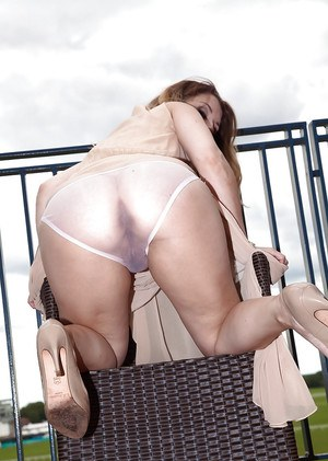 Aged lady in dress and high heels spreading hairy pussy outdoors