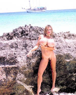 Mature beach babe Busty Dusty flaunting monster tits and tight ass outdoors