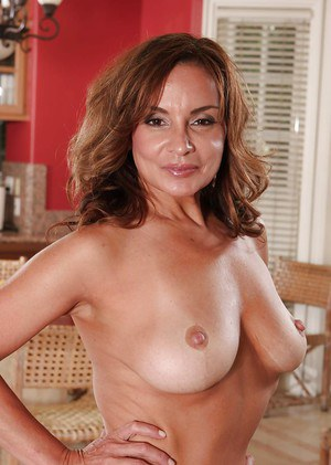 Aged French pornstar Rebecca Bardoux freeing big mature tits from lingerie