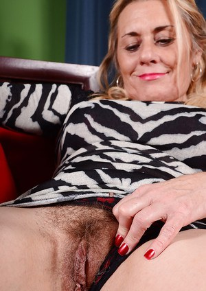 Mature dame Cristine Ruby sliding panties to one side to bare hairy cooter