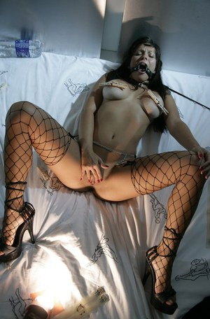 Handcuffed brunette babe in mesh stockings masturbates pussy and anus