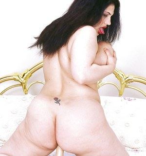 Tattooed brunette BBW unleashes huge boobs and thong clad ass