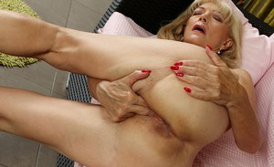 Ugly blonde granny Janet Lesley bares small saggy tits before masturbating