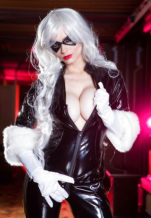 Platinum blonde babe in mask unleashes large tits from latex uniform