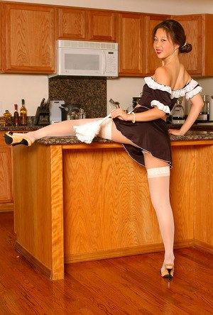 Amateur Asian babe in maid's uniform and stockings strutting in kitchen