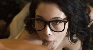 Glasses adorned brunette pornstar Noelle Easton giving bj in office