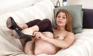 Mature broad in high heels removes spandex pants to reveal hairy pussy
