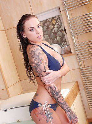 Tattooed solo girl Daniella Mae releasing big tits from bikini in bathroom