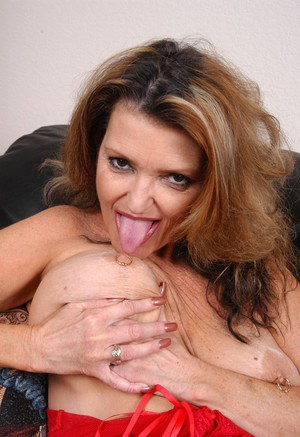 Busty mature lady with piercings licking own nipples before spreading cunt
