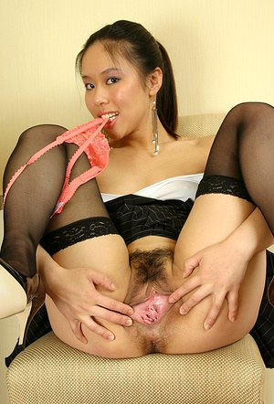 Amateur Asian chick slips off panties to reveal hairy pussy in high heels