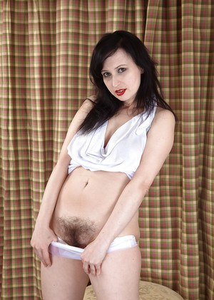 High heel wearing older brunette slipping off panties to expose hairy pussy