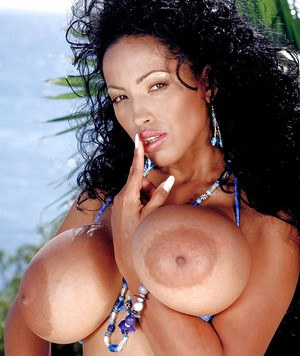 Aged Latina pornstar Busty Angelique frees big boobs and pussy from bikini
