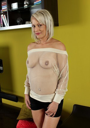Mature blonde woman Vanessa Moore freeing big tits from see thru mesh top