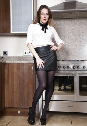 Solo girl Samantha Bentley struts in kitchen in leather skirt and stockings