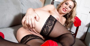 Stocking clad mature lady Sasha Sean revealing big tits and shaved pussy