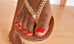 Older black woman showing off sexy legs and painted toenails