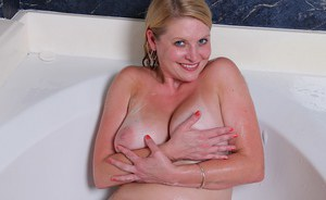Older plumper Lynn Miller showing off big wet tits in bathtub