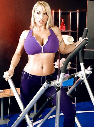 Blonde babe Holly Halston exposing huge MILF tits on workout machine