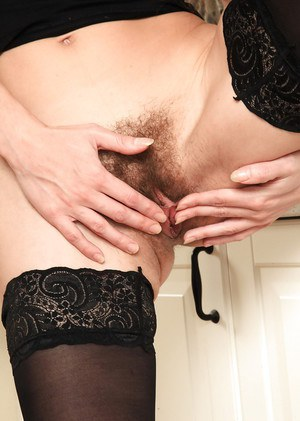 Stocking and high heel garbed mature woman exposing hairy cunt in kitchen