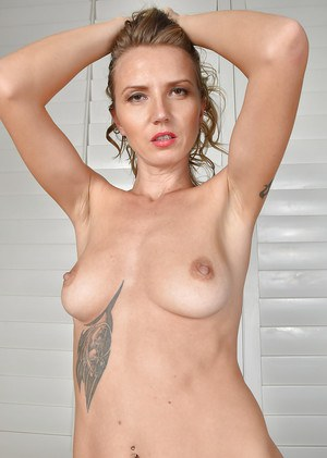 Older lady with tattoos exposing big natural tits and shaved pussy