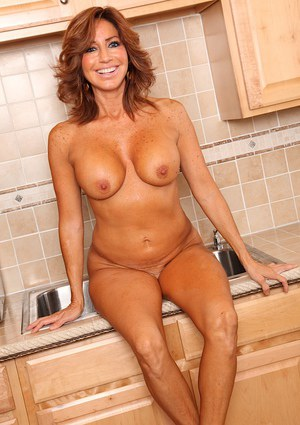 Mature Latina pornstar Tara Holiday baring large juggs in kitchen