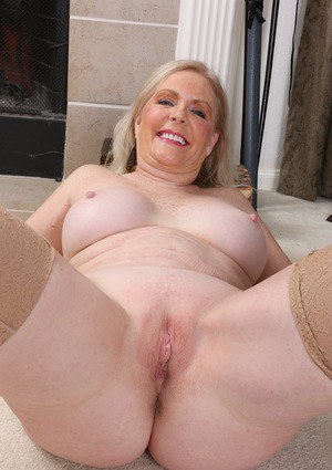 Mature lady Judy Belkins baring large tits and erect nipples in stockings
