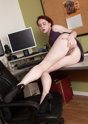 Aged office worker Annabelle Lee sliding panties aside to expose hairy cunt
