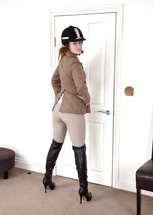 Mature woman in horse riding apparel revealing hairy cunt while undressing