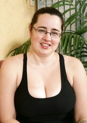 Mature plumper in glasses baring big breasts and hairy vagina