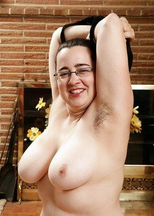 Mature plumper with hairy legs unveiling large hanging tits in glasses