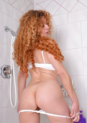 Busty mature woman with hairy twat sheds lingerie in shower before pissing