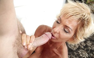 Blonde mom with large boobs giving big cock blowjob on knees