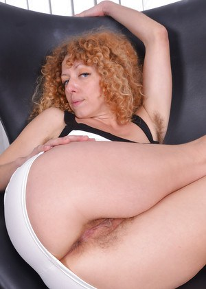 Mature redhead with small tits showing off hairy underarms and vagina