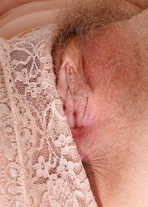 Mature redhead solo girl Leona exposing hairy cunt in nylons