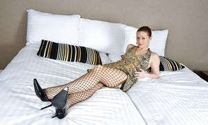 Mature woman Mischelle removing fishnet pantyhose from long legs