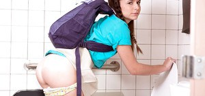 Young girl Kharlie Stone pulling down schoolgirl panties to pee in toilet