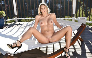 Older blond model delving fingers into shaved cunt after stripping outdoors