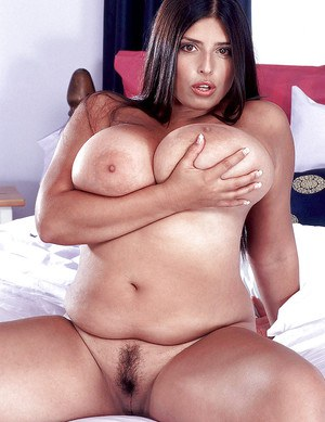 Plump Latina pornstar Kerry Marie revealing hooters and hairy muff