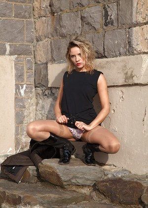 Clothed MILF model Regina baring long legs and muff in tan hose and boots