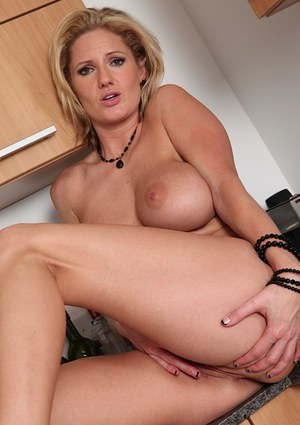 Blonde MILF Zoe Zale exposing round boobs in fishnets on kitchen counter