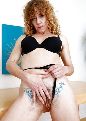 Aged hirsute woman Leona spreading hairy ginger pussy wide open