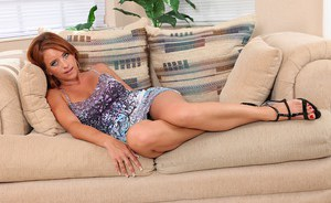 Older redhead woman Olivia Sinclair baring big tits and pink pussy in heels