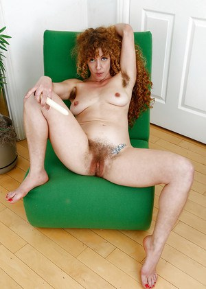 Aged hirsute model Leona inserting sex toy into wide open beaver
