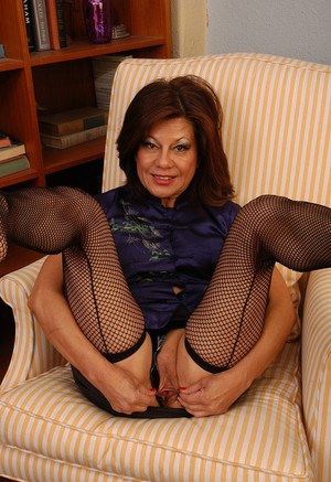 Older lady in miniskirt and mesh stockings stripping to display bald cunt