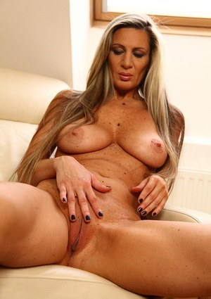 Blonde MILF Mercedes Silver freeing large tits and shaved cunt from dress