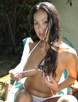 Asian first timer Milla freeing wet pussy from bikini bottoms outdoors