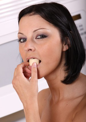 Older brunette lady Michelle flaunting round boobs while eating a banana