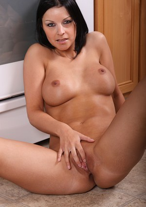 Mature brunette Michelle exposing large tits and bald cunt in kitchen