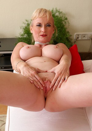 Older blonde dame Monik revealing big boobs and pink pussy in red high heels