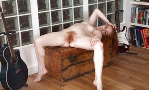 Older redhead model Tia Jones freeing hairy cooter from pink underwear